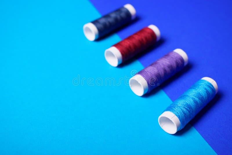 Hilos de coser rojos y azules imagen de archivo