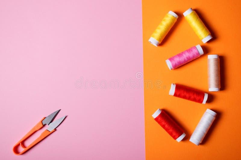 Hilos de coser y tijeras coloridos en fondo brillante imagen de archivo libre de regalías