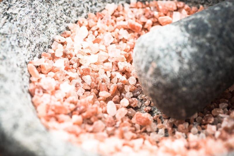 Himalajski menchii soli ziarno w granitowym moździerzu lub tłuczku fotografia royalty free