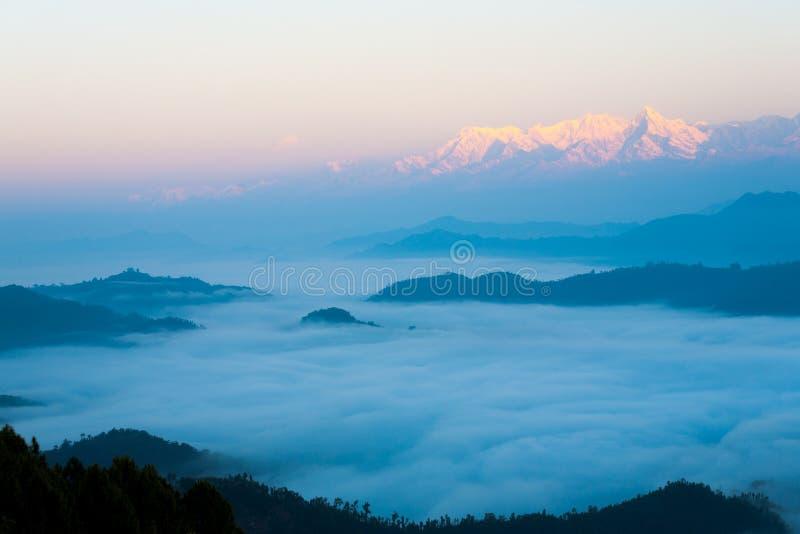 Himalayan bergskedja över havet av molngryning arkivbilder