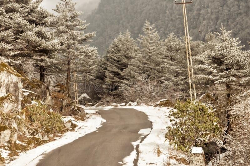 Himalayan bergväg för blåsigt snöig dimmigt halt lerigt plant moment i vinter Leh Manali huvudväg, Jammu and Kashmir, Indien, Asi arkivfoto