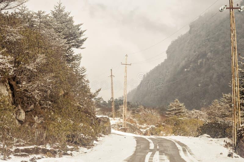 Himalayan bergväg för blåsigt snöig dimmigt halt lerigt plant moment i vinter Leh Manali huvudväg, Jammu and Kashmir, Indien, Asi arkivfoton