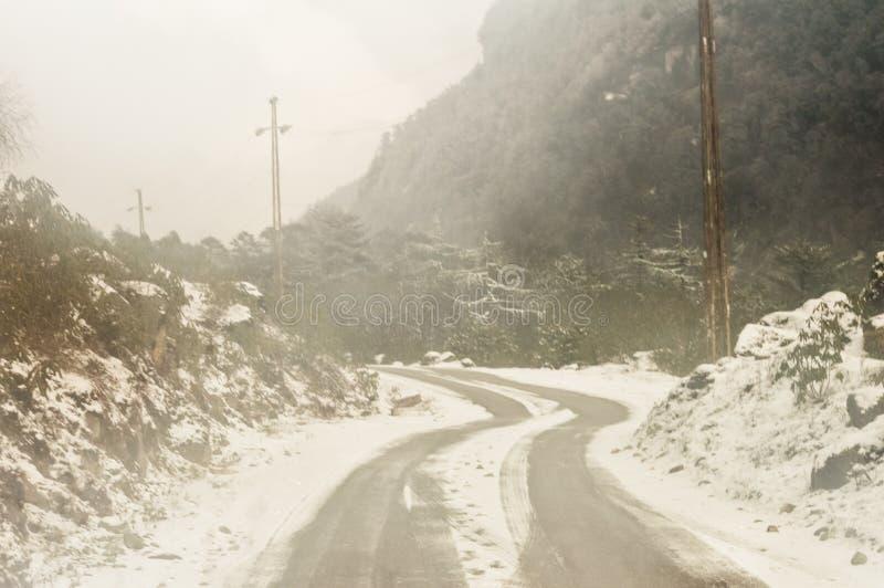 Himalayan bergväg för blåsigt snöig dimmigt halt lerigt plant moment i vinter Leh Manali huvudväg, Jammu and Kashmir, Indien, Asi royaltyfri foto