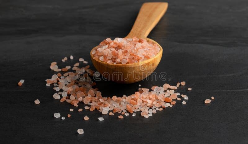 Himalayan rosa färger saltar spill från träskeden arkivbild