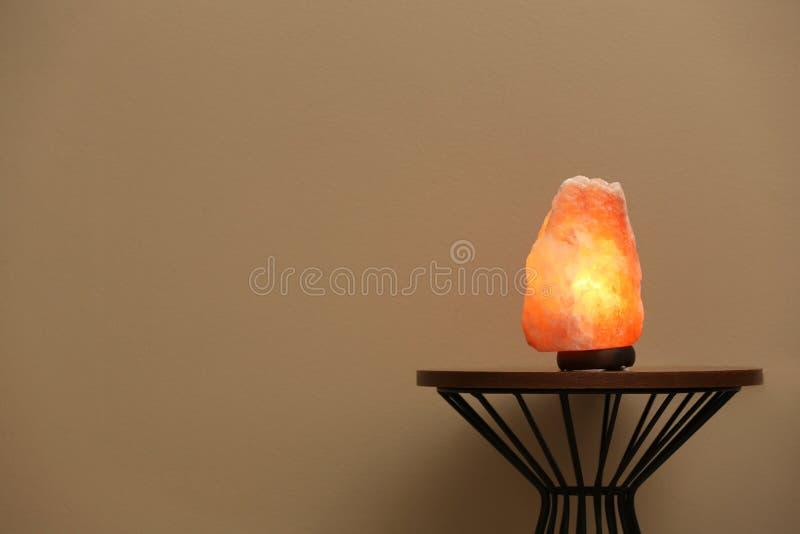 Himalayan salt lamp on  against  beige background. Space for text. Himalayan salt lamp on table against  beige background. Space for text stock photos
