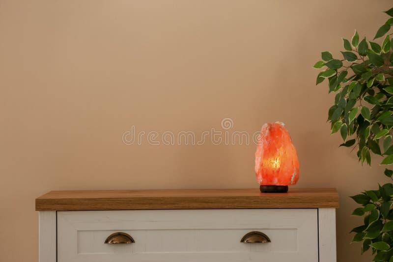 Himalayan salt lamp on cabinet stock photo