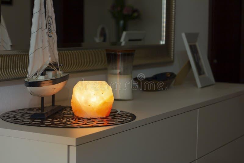 Himalayan salt lamp glowing in dark stock photo