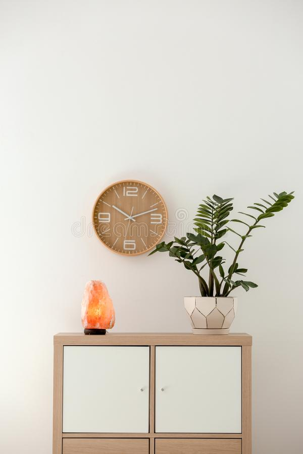 Himalayan salt lamp and plant on cabinet royalty free stock photography