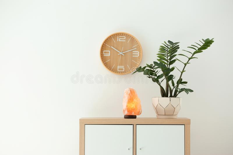 Himalayan salt lamp and plant on cabinet. Against white wall stock photo