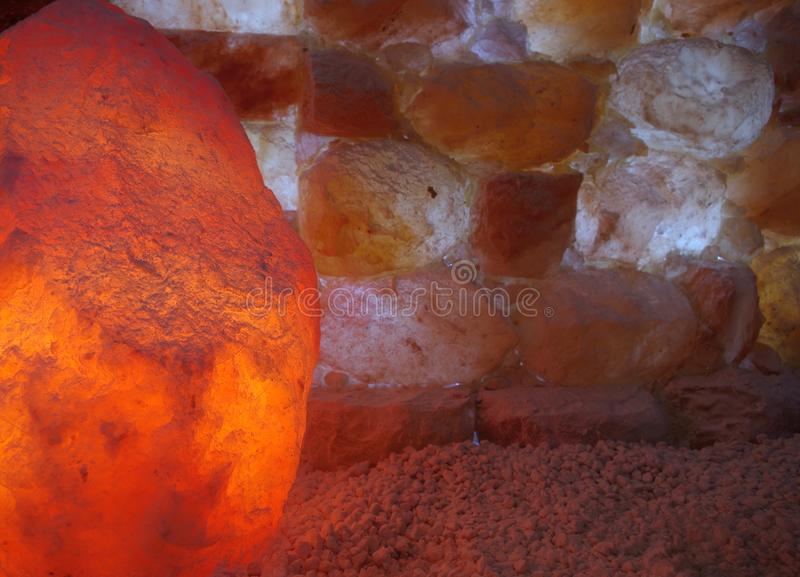 Himalayan Salt Lamp and Salt Stones. Himalayan salt lamp and salt stone wall in a halotherapy spa royalty free stock images