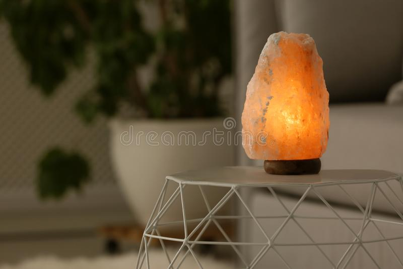 Himalayan salt lamp on table. Against blurred background stock photography