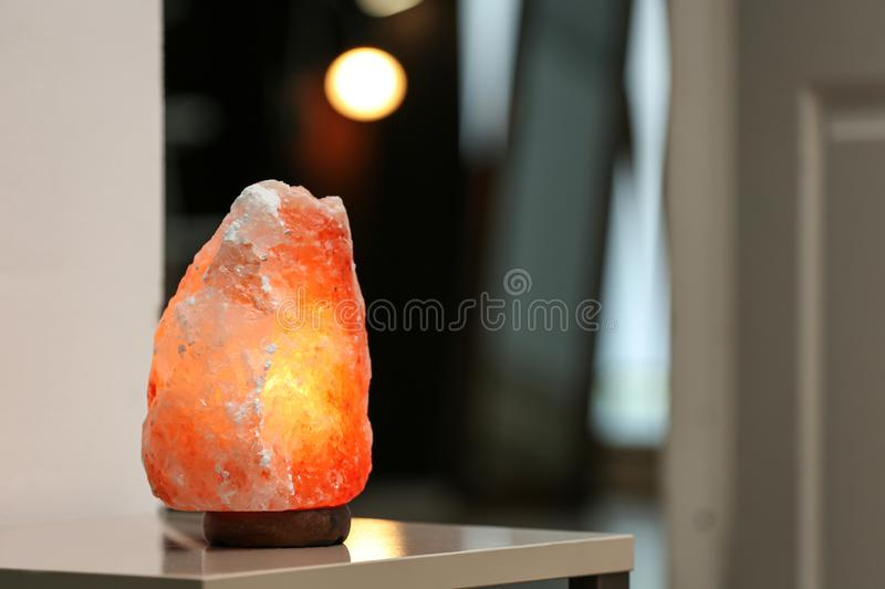 Himalayan salt lamp on table in room.  for text. Himalayan salt lamp on table in room. Space for text royalty free stock photo