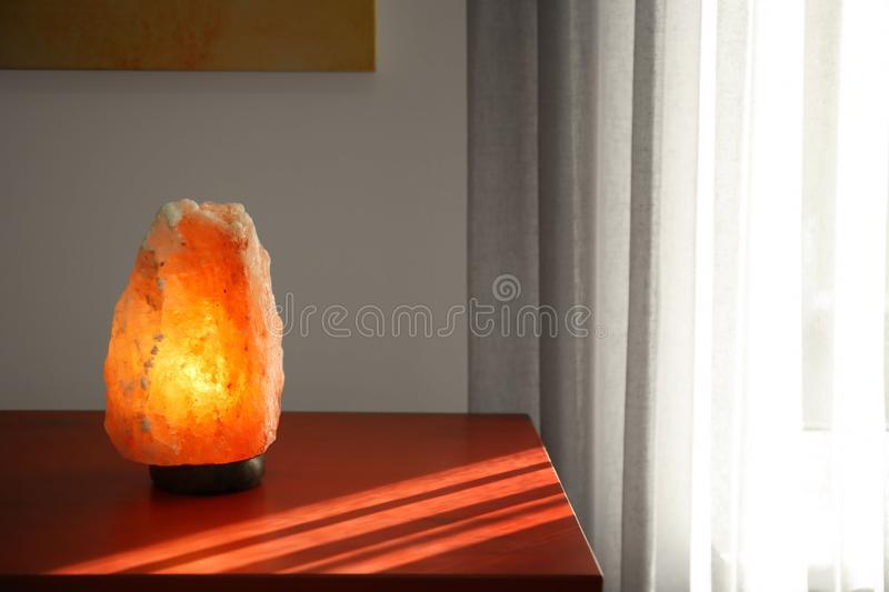 Himalayan salt lamp on wooden cabinet. Indoors royalty free stock images