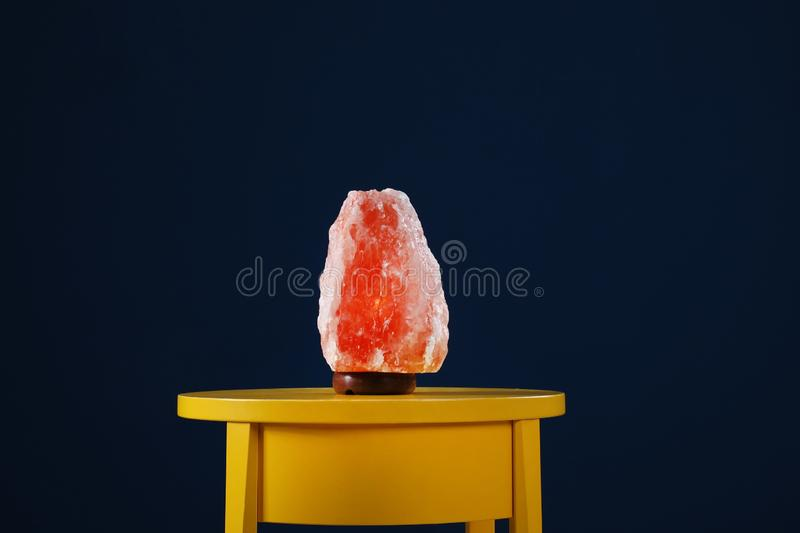 Himalayan salt lamp on yellow table against blue background. Himalayan salt lamp on yellow table against dark blue background stock image