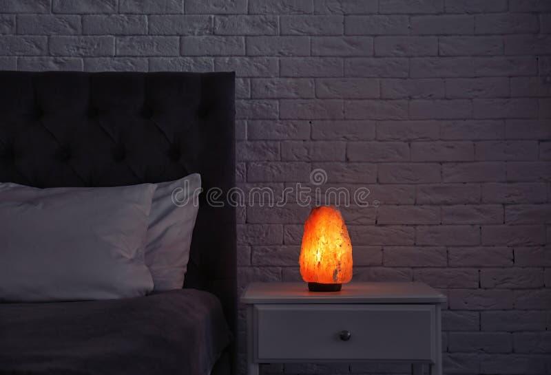 Himalayan salt lampa som glöder på nattduksbordet arkivbilder