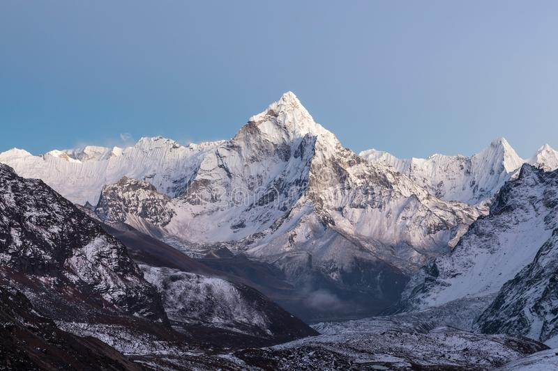 Himalayan scenery of mountain Ama Dablam summit. Highlands landscape of the mountain range in blue and purple morning lights. Beautiful background for your stock photos
