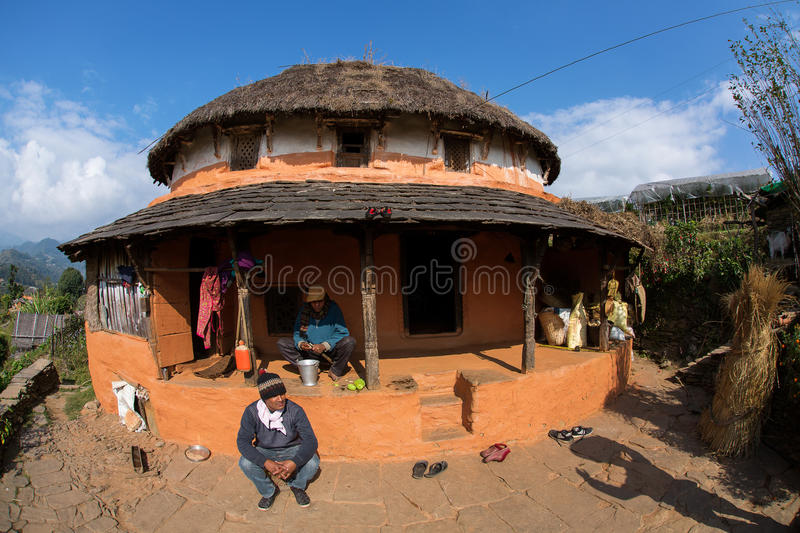 HIMALAYAN VILLAGE, NEPAL - NOVEMBER 25: Unkown man sitting in fron of traditional house of Himalayan Village on November 25, 2014. In HIMALAYAN VILLAGE, Nepal stock image