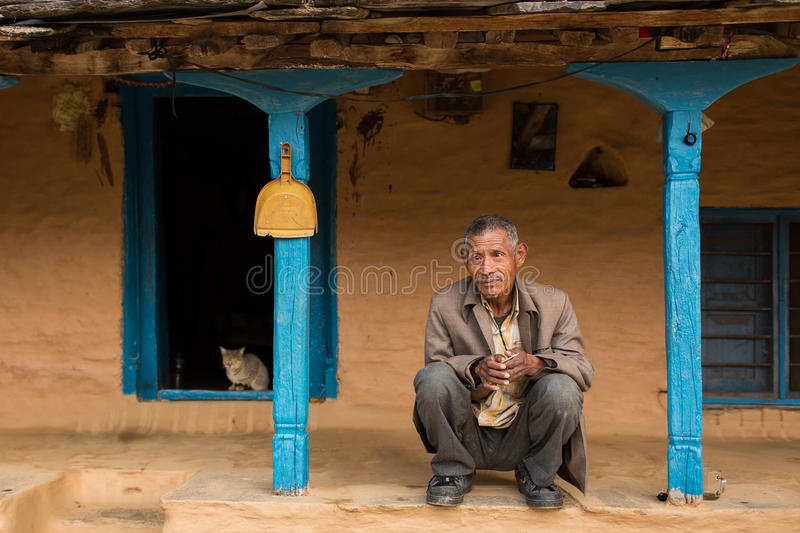 HIMALAYAN VILLAGE, NEPAL - NOVEMBER 25: Unkown man sitting in fron of traditional house of Himalayan Village on November 25, 2014. In HIMALAYAN VILLAGE, Nepal royalty free stock photography