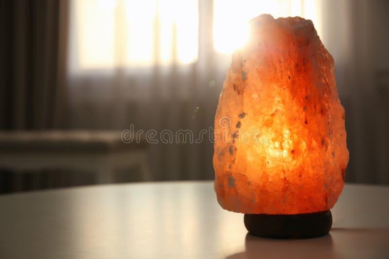 Himalayan zoute lamp op lijst stock afbeelding