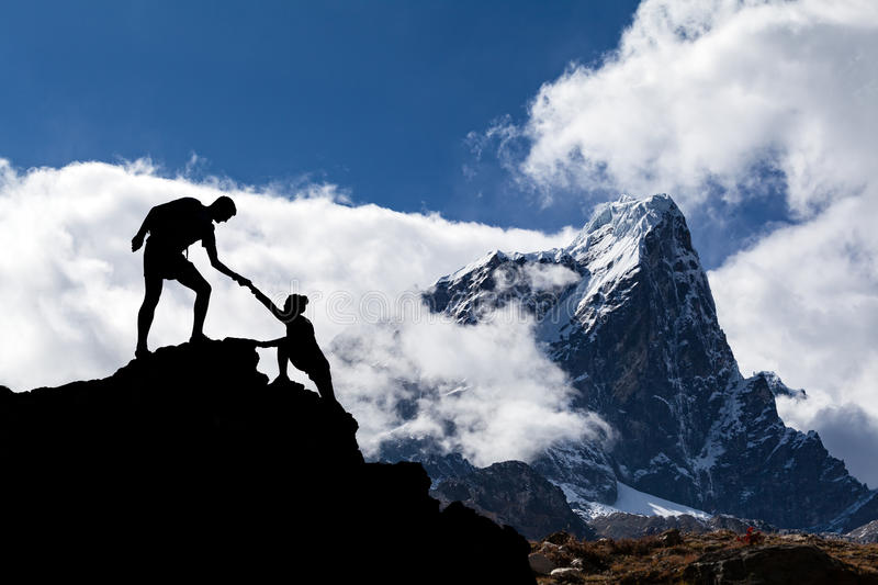 Teamwork couple hikers silhouette in mountains, climbers team stock photography