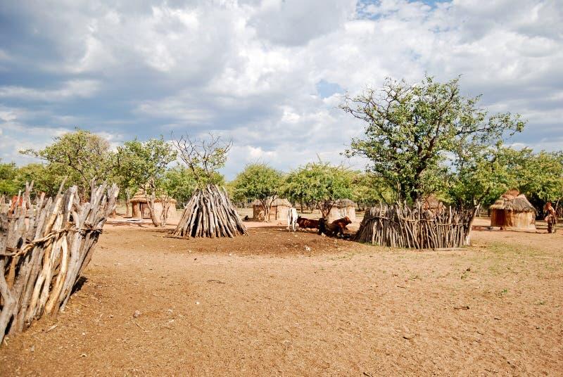 Himba by med traditionella kojor nära den Etosha nationalparken i Namibia royaltyfria bilder