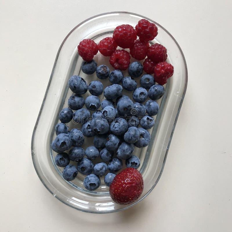 Himbeeren, Blaubeeren u. eine einzelne Erdbeere auf einem Glasteller - STRENGER VEGETARIER - VEGETARIER stockfotos