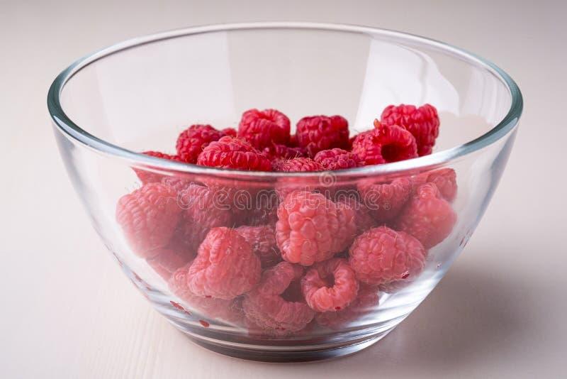 Himbeerrote Beeren im geschmackvollen Bonbon der transparenten Glasschüssel-Platte hell auf weißem Hintergrundkopien-Raummakro stockfoto