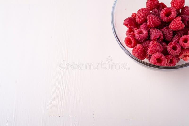 Himbeerrote Beeren im geschmackvollen Bonbon der transparenten Glasschüssel-Platte hell auf weißem Hintergrundkopien-Raummakro lizenzfreie stockfotografie