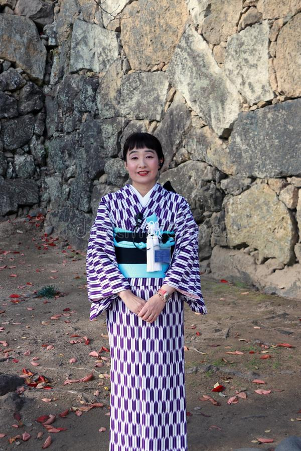 Kind and pleasant of receptionist in Kimono dress on purple and white color at Himeji Castle. stock photography