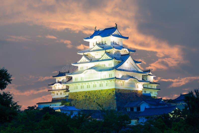 dramatic evening orange sunset sky behind lighted himeji jo castle using telephoto lense for magnified close up details in himeji japan after 2015
