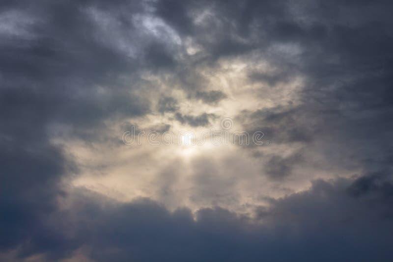 Himlen med mörka stormiga moln, till och med som sollooks_en arkivfoton
