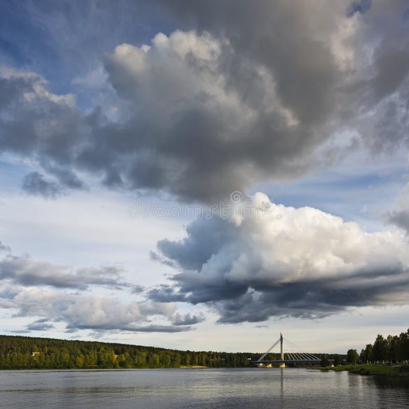 Himlen med moln och en bro över floden finland arkivfoton