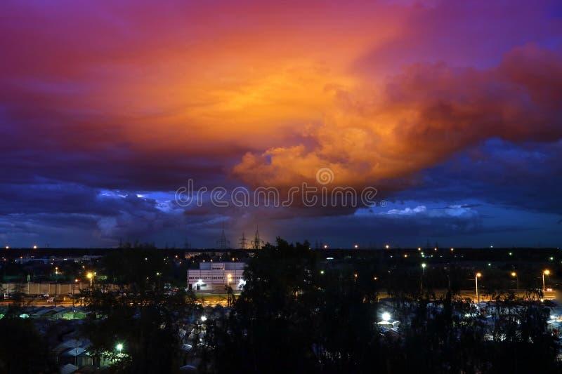 Himlen på natten med ljusa röda moln i strålarna av solen arkivfoto