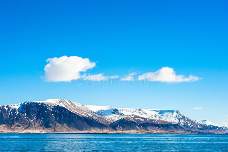 Himmel über einem Berg im Ozean lizenzfreie stockfotos