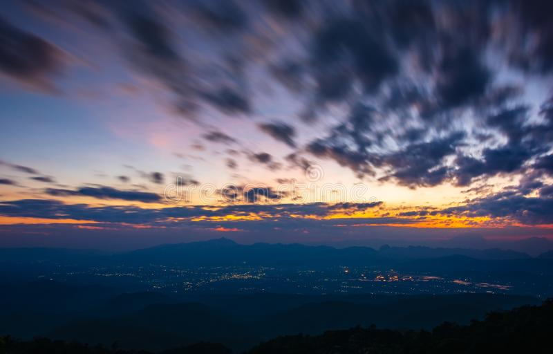 Himmel för Colorfull solnedgångskymning med molnflöde över liten stad arkivfoto