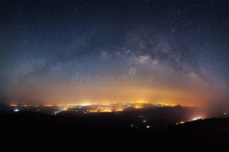 Himmel för den stjärnklara natten med galaxen för den mjölkaktiga vägen och staden tänder på Phutabb royaltyfria bilder