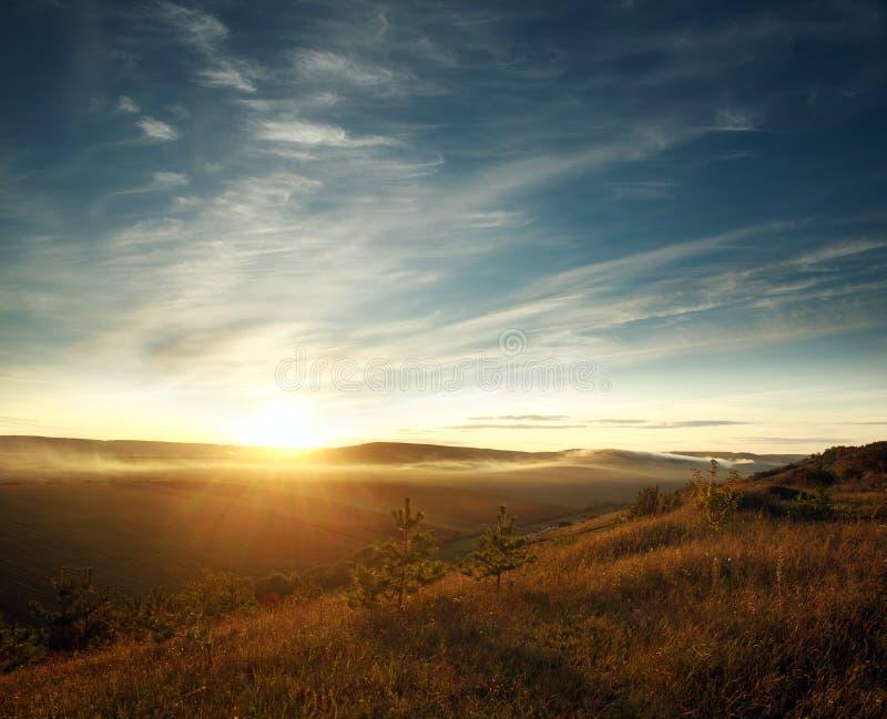 Himmel i strålar av inställningssolen över kullarna och fälten royaltyfri bild