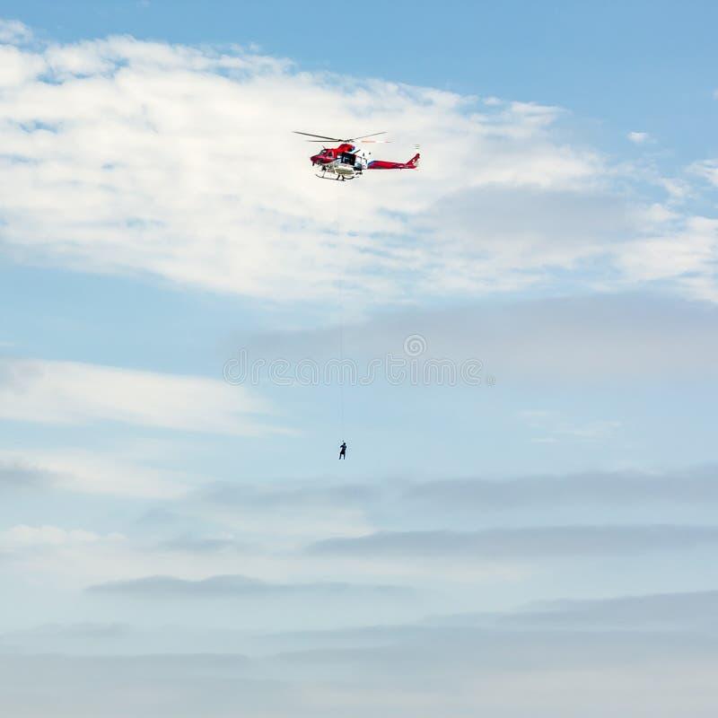 Himmel mit einer Person, die durch ein Seil auf einem Zerhacker hängt lizenzfreie stockbilder