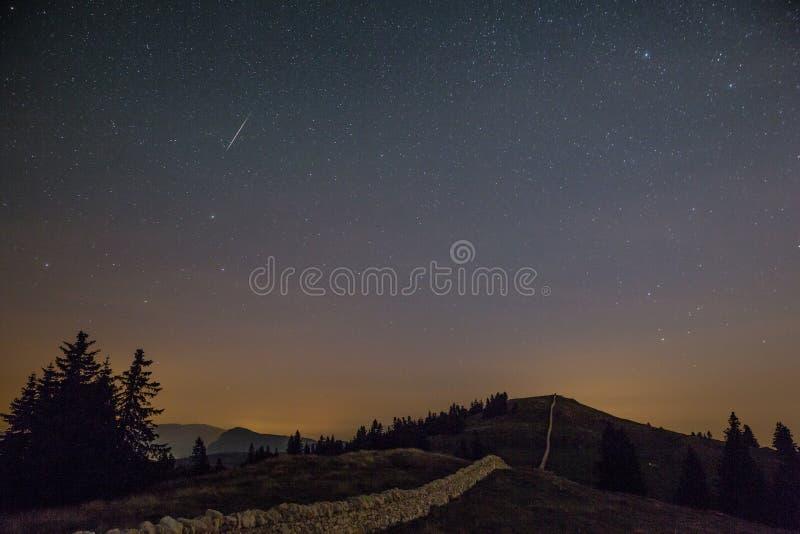 Himmel och Shooting Stars för stjärnklar natt över berg fotografering för bildbyråer