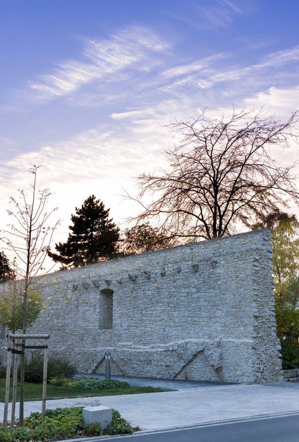 Himmel och stadsväggen med parkerar och träd i solnedgången som glöder i b royaltyfri bild