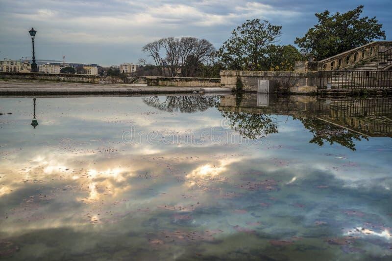 Himmel reflekterade i vatten på det 18th århundradevattentornet, Montpellier, Frankrike arkivfoton