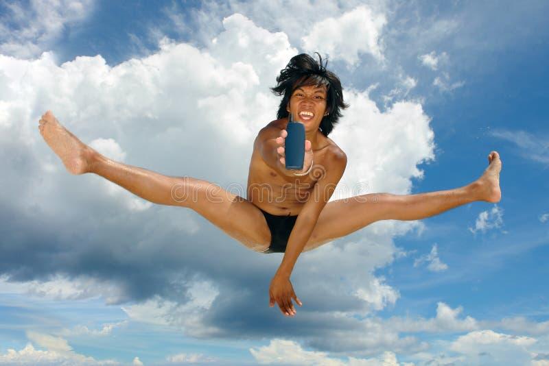 Himmelhoher Sprung, der Handy durch asiatischen tropischen Jungen bekanntmacht. stockfoto
