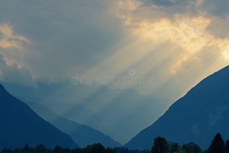 Himmlische goldene Lichtstrahlen, die durch Wolken hinunter ins Tal und in die Berge strahlen lizenzfreie stockfotos