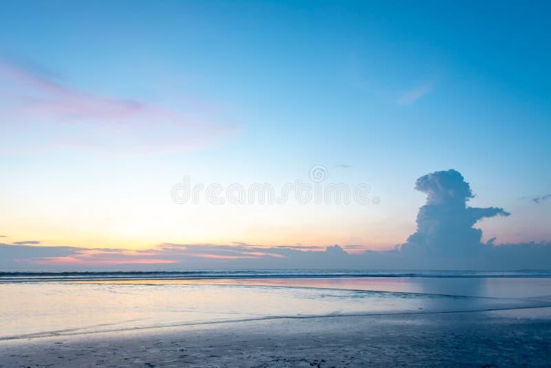 Himmlischer Sonnenuntergang-Strand mit Kumulus Congestus-Wolke im orange Sonnenlicht-Hintergrund stockfoto
