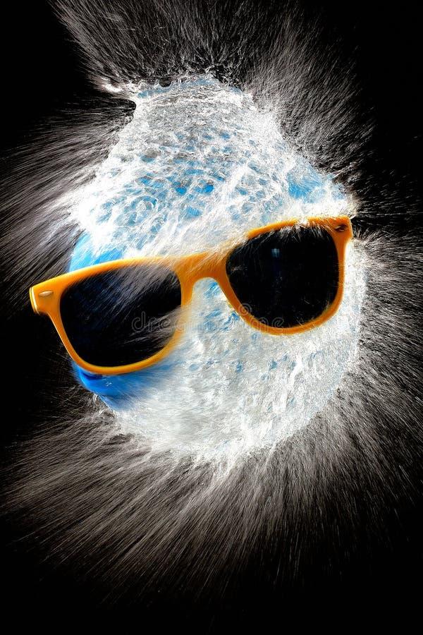 Hinche la explosión con agua azul y los vidrios de sol en estudio imagenes de archivo