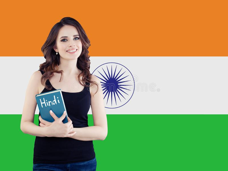 Hindi language school concept. Perfect brunette woman student with book on the India flag background.  stock images