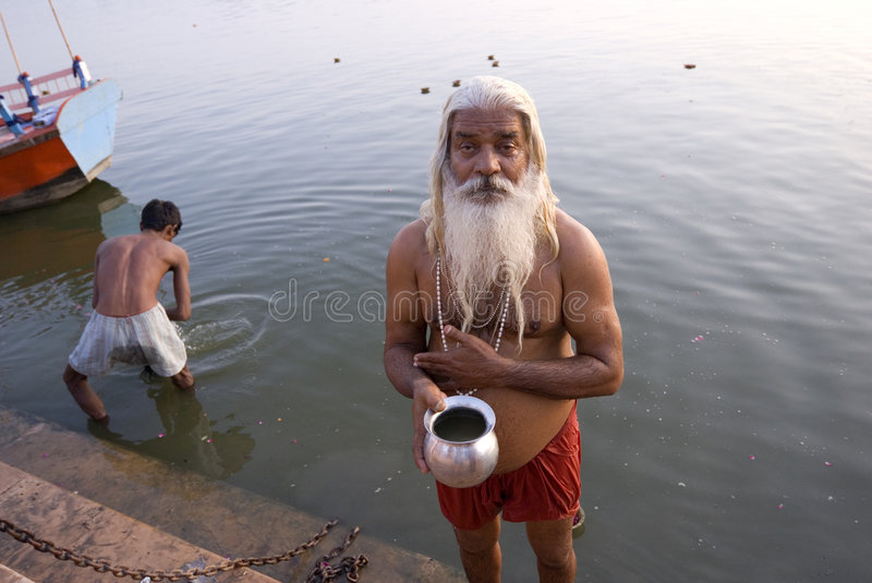 Hindoo disciplinant. An old Hindoo disciplinant is begging at the ghat on river Yamyna after his moring bath in the holy river stock photo