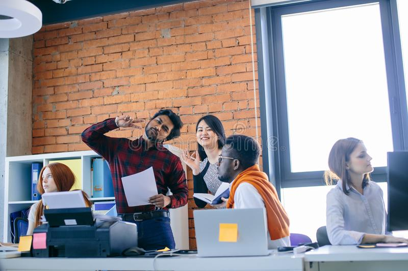 Hindoo man and Chinese woman are posing to the camera at workplace. Hindoo men and Chinese women in casual outfit are posing to the camera at workplace in the royalty free stock photography