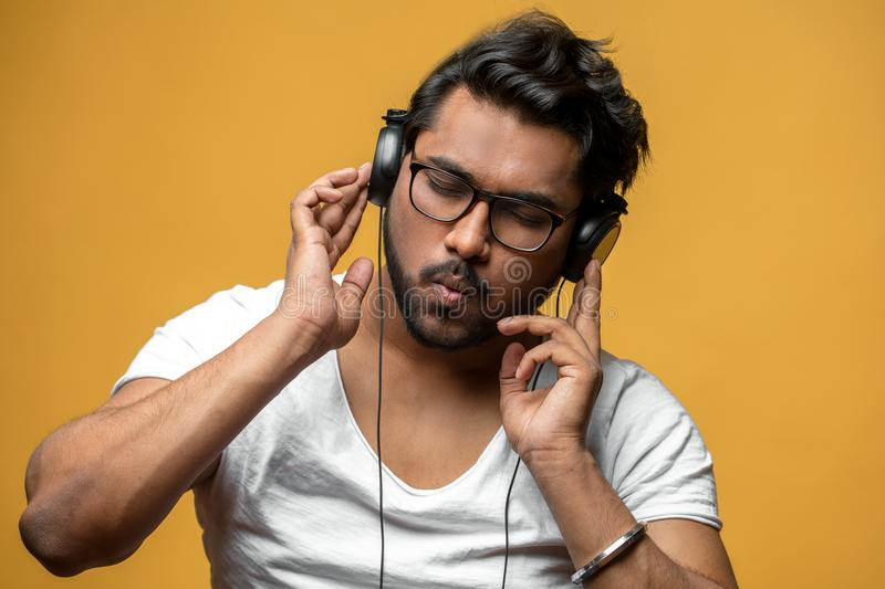 Hindoo young man is mad at music. Isolated on the yellow background. music taste. put out song. hipster spending time on music royalty free stock images