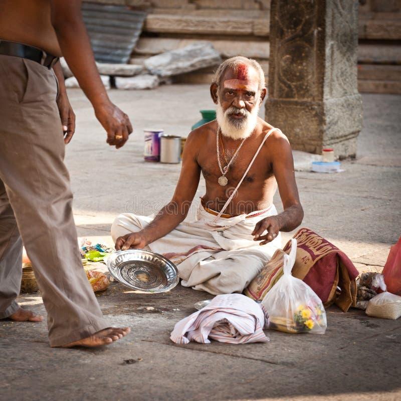 Hindu Brahmin with religious attributes blessing people at Meenakshi Temple. India, Madurai, Tamil Nadu stock photo